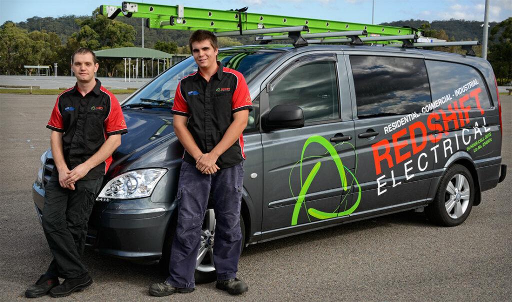 electricians standing by working van